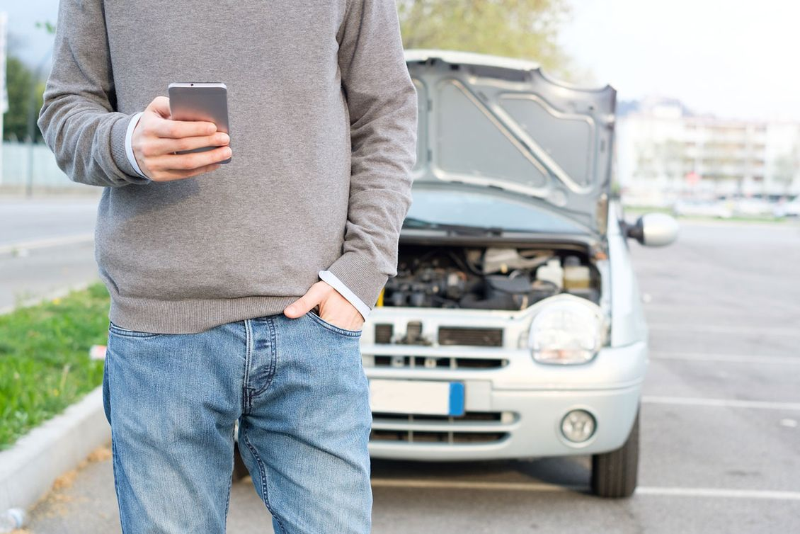 A customer on his phone to a mechanic after breaking down