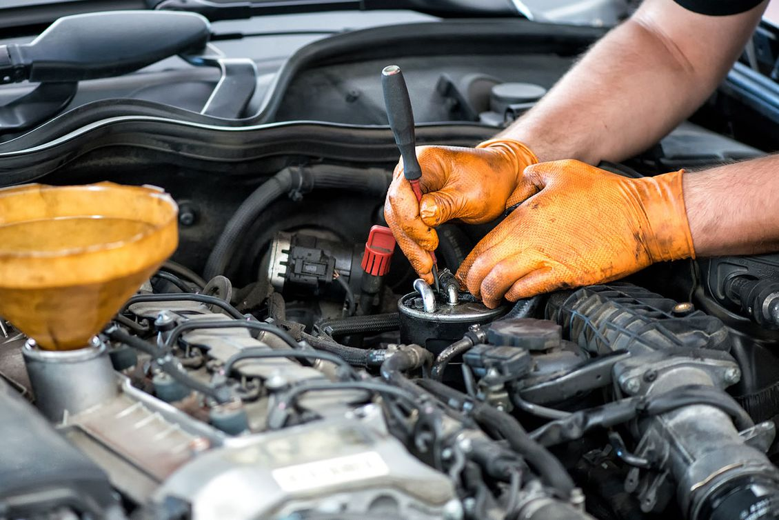 A mechanic making repairs to a customer car
